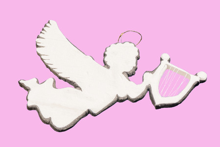 simbolos religiosos: Silver flying angel gigurine ornament holding harp isolated on pink background Foto de archivo