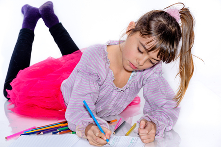 eight year old: Beautiful eight year old girl drawing with color pencils Stock Photo