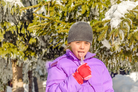 icicle: Little girl licking icicle Stock Photo