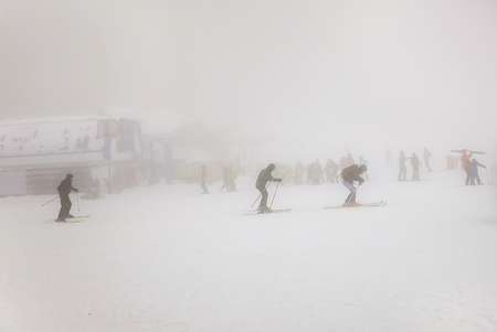 extreme weather: People skiing on extreme weather with fog and zero visibility