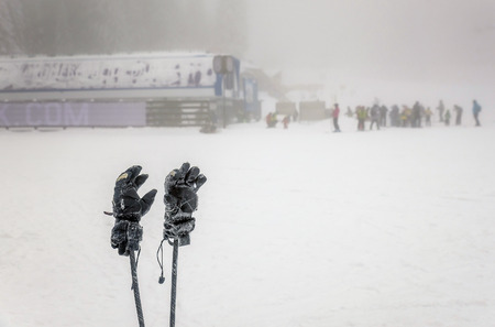 extreme weather: Winter gloves and skii poles with people skiing on extreme weather with fog in the background Stock Photo