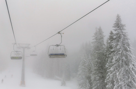 ski lift: Chairs of a ski lift heading into the fog