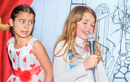 nine years old: Little girls singing with microphone