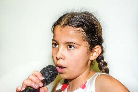 nine year old: Nine year old girl singing with microphone