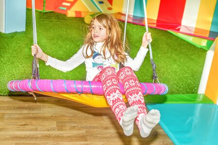nine years old: Little girl swinging on the swing in the  playground Stock Photo