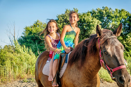 Two little girls riding horse in the summer in Ada Bojana, Montenegro