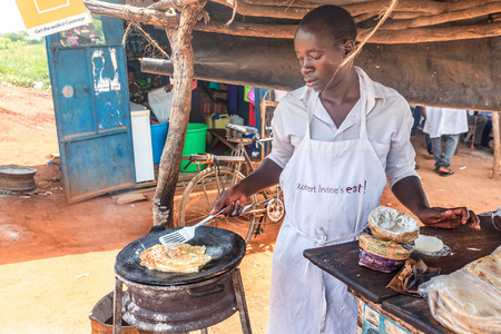 ugandan: Uganda, Africa- March 31, 2016: Preparation of traditional Ugandan breakfast Rolex made with chapati and eggs Editorial
