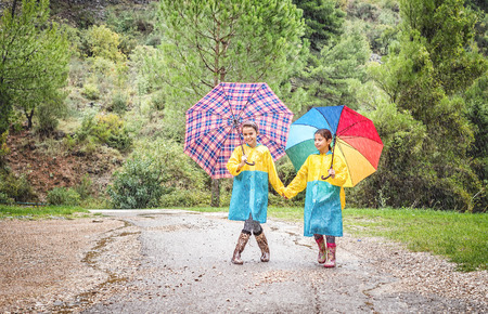 Children with colorful rainbow umbrella,raincoats and waterproof boots play  in the rain Stock Photo