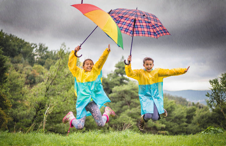 Children with colorful rainbow umbrella,raincoats and waterproof boots jump in the rain