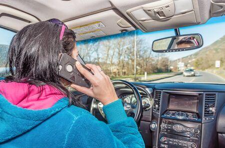 Woman using phone while driving a car
