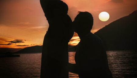 Couple silhouette flirting in the sunset Imagens