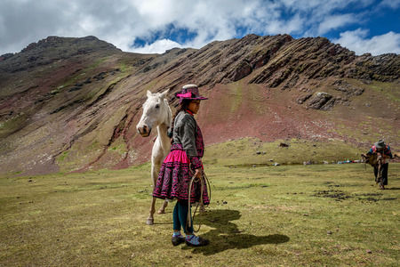 Woman with a horse on Vinicunca aka Rainbow Mountain in the region of Cusco, Peru