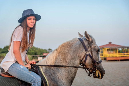 Girl with a hat riding a horse