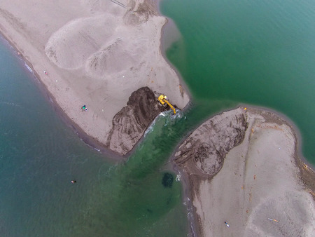 Buldozer diggin sand to open the river mouth of river Bojana, Montenegro Banque d'images