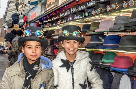 Two beautiful little girls with hats in London