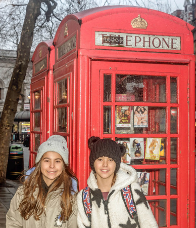 London, UK- January 11, 2018:Two little girls standing in front of English Telephone Booth in London