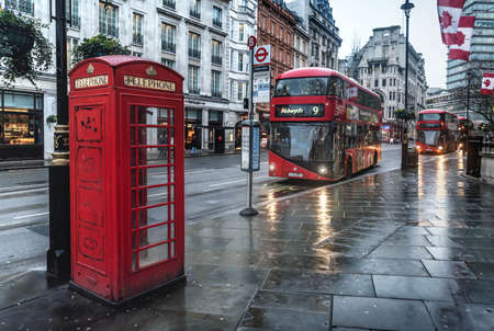 London, UK- January 11, 2018: Telephone Booth and a modern double decker bus on the street in London, UK