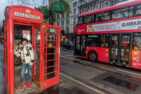 London, UK- January 11, 2018: Little girl talking on the phone in Telephone Booth in London Editorial