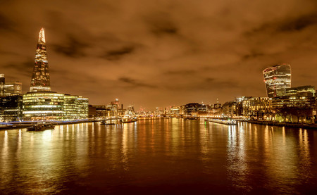 A view of the River Thames with the financial skyscrapers of the city of London at night, UK