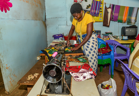 Nairobi, Kenya- March 5, 2016:Woman Tailor sewing clothes with vintage sewing machine