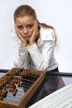 A sad girl with a keyboard and abacus, on the table