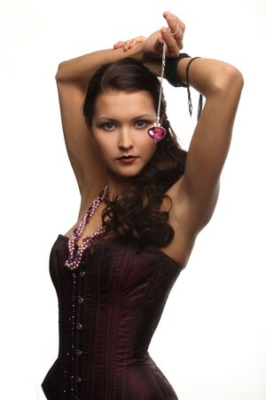 girl in a corset holding a decoration in the form of heart