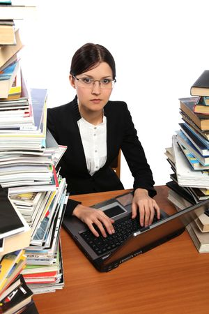 she works with the computer (a lot of books on the table) Stock Photo