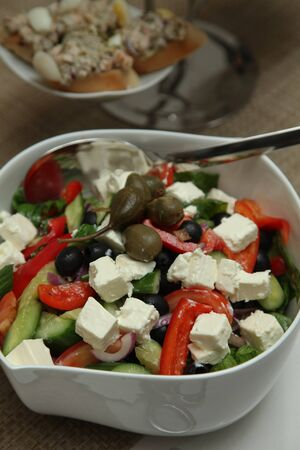 cup of Greek salad with feta cheese, fresh herbs, olives for a buffet