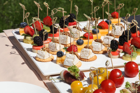 Beautifully decorated catering banquet table with different food snacks and appetizers with sandwich, fresh fruits on corporate christmas birthday party event or wedding celebration