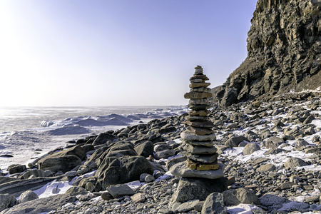 Stone pyramid in winter on a rocky beach of a frozen bay covered with snow