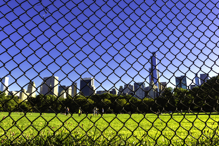 Central Park lawn and Manhattan skyline behind the wire fence. Stock Photo
