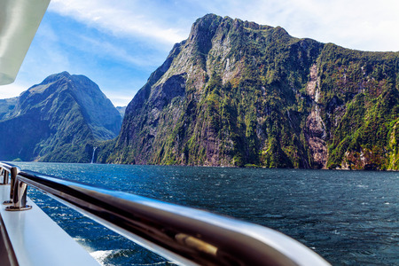 Rocky mountains and waterfall in Milford sound, image taken from cruise ferry Imagens