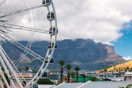 Ferris wheel at Waterfront in Cape Town and Table Mountain covered with clouds