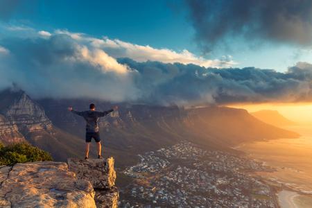 Jeune homme debout sur le bord au sommet de la montagne Lion's Head à Cape Town avec une belle vue sur le coucher du soleil