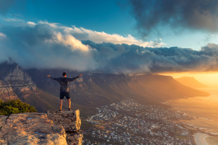 Young man standing on the edge at the top of Lion's head mountain in Cape Town with a beautiful sunset view Imagens