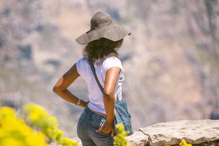 Young african woman in a hat admiring views in South Africa