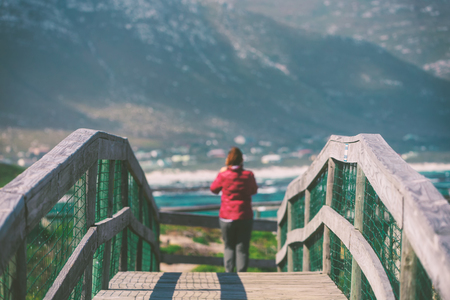 Wooden pedestrian bridge and tourist woman in Bettys bay, South Africa Stock Photo