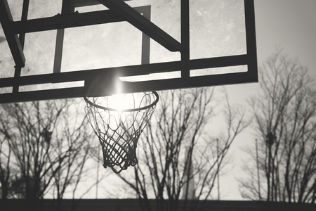 Monochrome image of old basketball backboard and sun inside the rim 写真素材 - 120736838