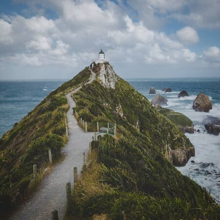 Nugget Point lighthouse trail and rocks in the ocean in Otago, New Zealand