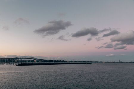 Evening view of Auckland bridge and calm water of the harbour