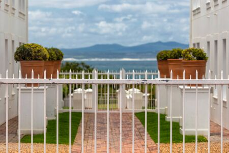 Seascape view between two white buildings and white fence in foreground Banco de Imagens