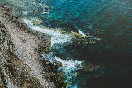 Aerial view of rocky coastline and turquoise sea water