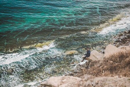 Man sitting on the edge of the rock with beautiful sea view