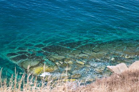 Top view of rocky coastline and turquoise sea water