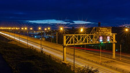 Night view of the bridge with traffic lights and cloudy dramatic sky in Vladivostok, Russia. Sign translation - Stopping and parking the vehicle on the bridge is prohibited.