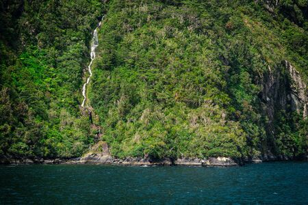 High waterfall in Milford Sound, New Zealand, picture taken from cruise ferry
