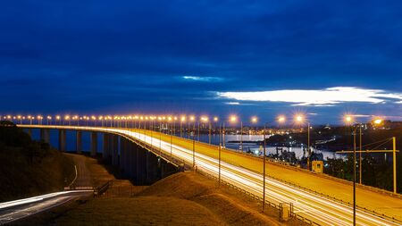 Night view of the bridge with traffic lights and cloudy dramatic sky in Vladivostok, Russia Stock Photo