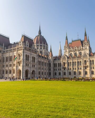 Hungarian Parliament famous building and green lawn on a sunny day, Budapest city