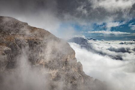Dramatic landscape view with rocky mountains covered with stormy clouds, Dolomites, Italy