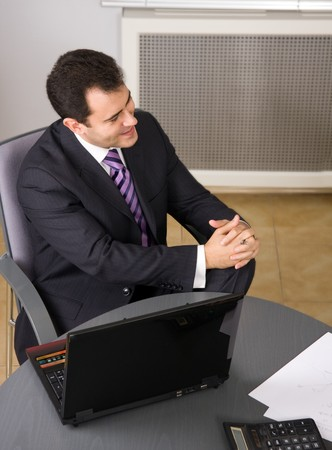 Businessman sitting in office with laptop in the office photo